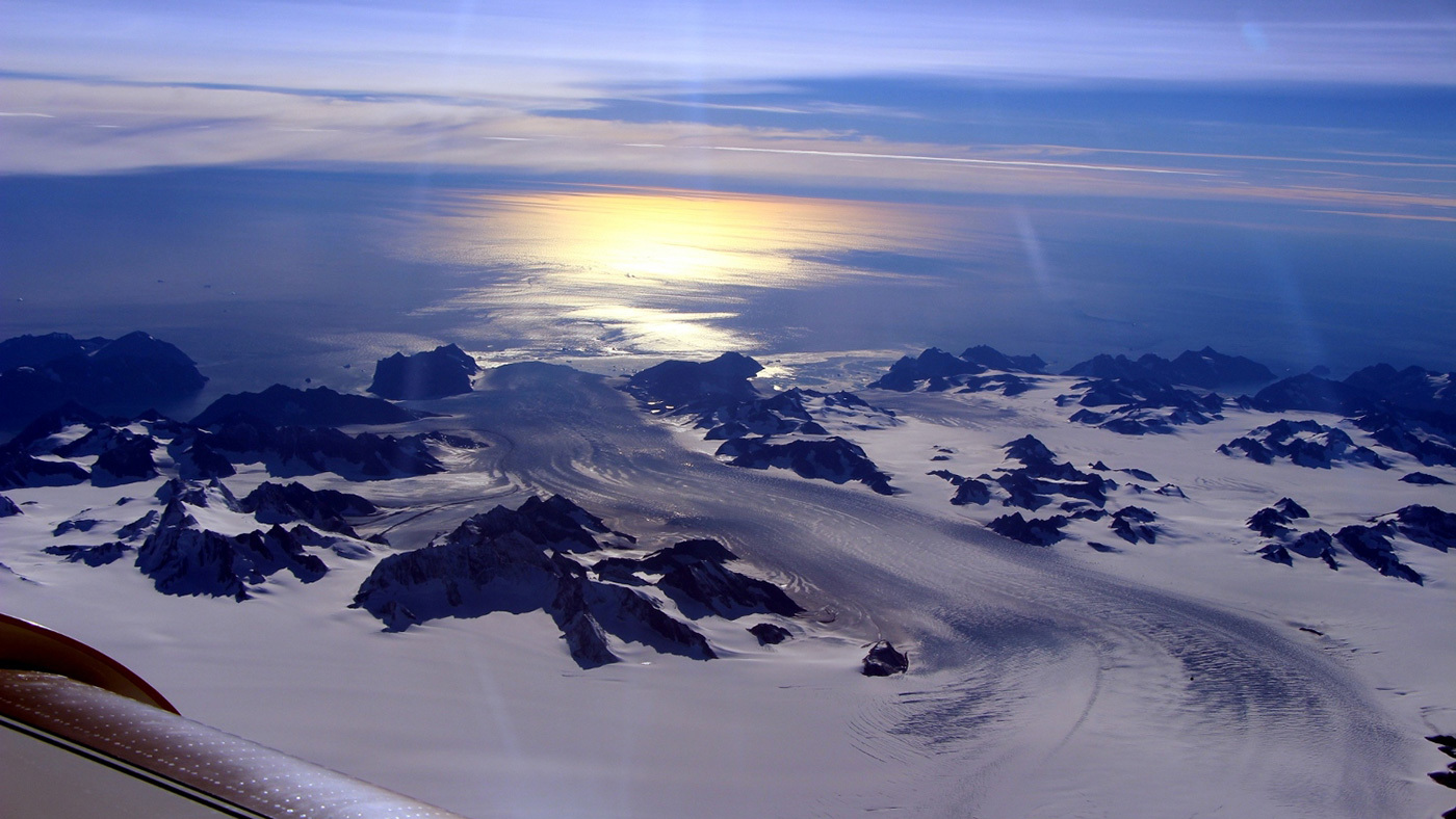 Greenland's Steenstrup Glacier, with the midmorning sun glinting off the Denmark Strait in the background. The image was taken during a NASA IceBridge airborne survey of the region in 2016. Credit: NASA/Operation IceBridge › Larger view