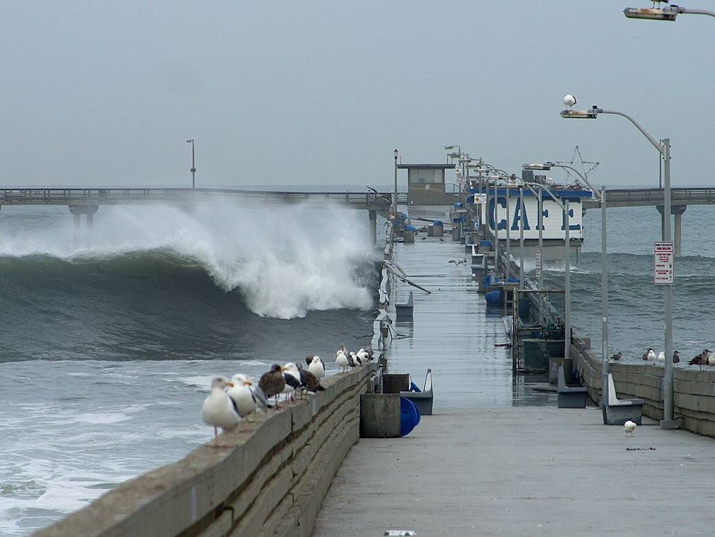 A big wave crashing over a pier in San Diego during the 2002 El Nino